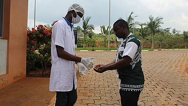 This photo shows two men, one wearing protective gear (face mask, hand gloves and a doctor's coat). He is offering hand sanitizer to the second man, at the gates of the clinic.