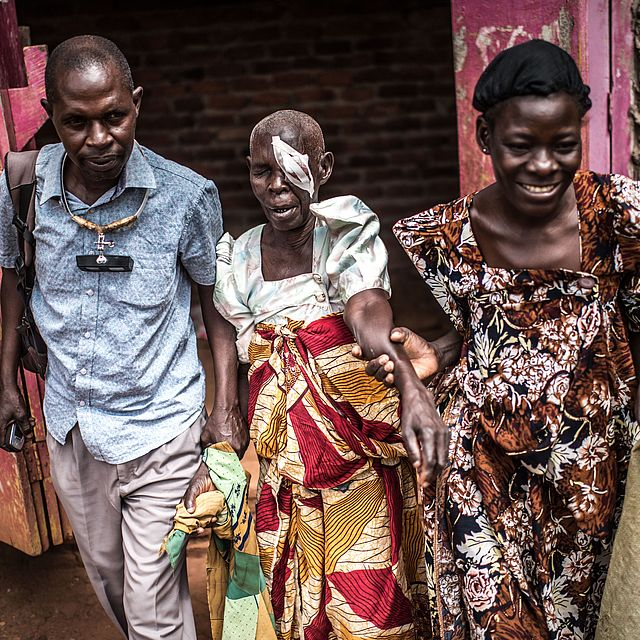 This photo shows an old Ugandan woman with an eye patch being helped by 2 people (a man and a woman)