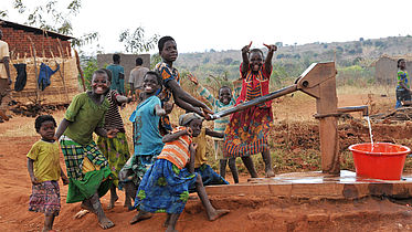 This photo shows a group of children at a water tap community point smiling and laughing together.
