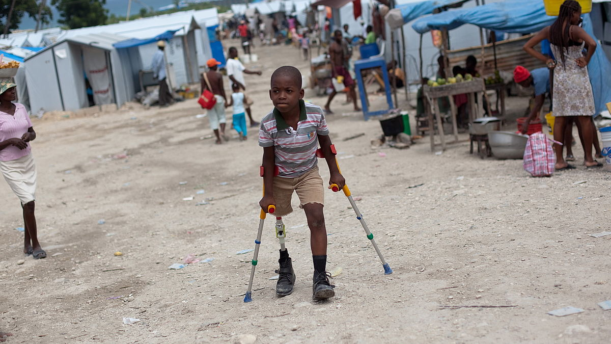 Sebastien (10) zips around the temporary tent camp where he lives after the earthquake.