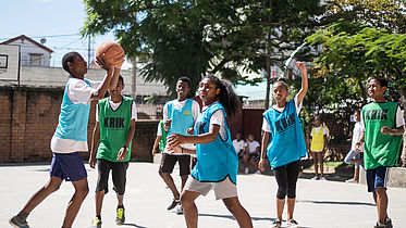 This photo shows young Madagascar girls and boys playing basketball on a court.
