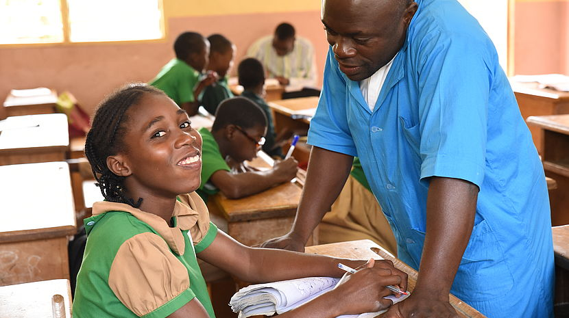 Matsiabo looks up from her schoolwork and smiles as her teacher comes to her desk.