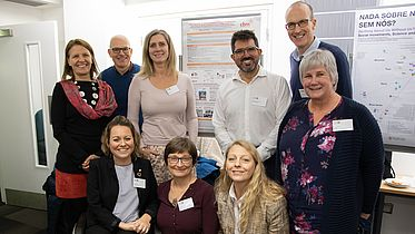 9 CBM colleagues gather for a photo in front of a CBM poster-presentation