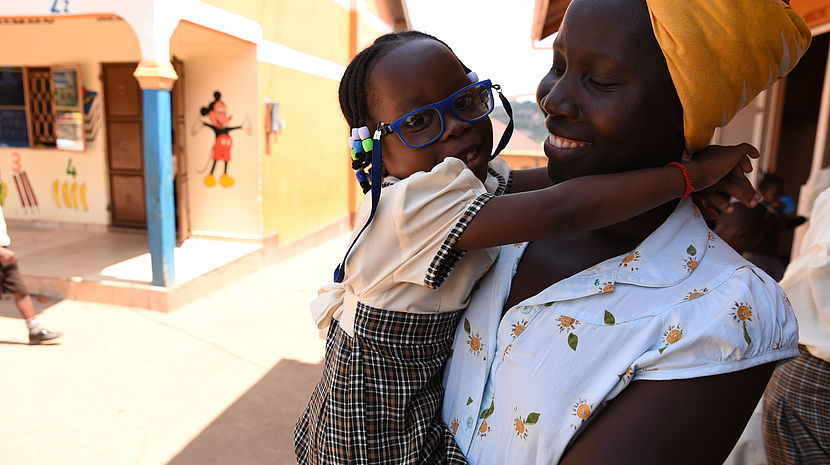 This photo shows a Ugandan woman wearing a headband holding her young daughter in her arms. Her daughter is wearing spectacles and has her arms around her mother.