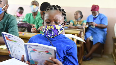 This photo shows a young 11 year old girl studying her notes in her classroom. She is wearing a mask and is surrounded by other students in the background.