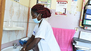 This photo shows a nurse wearing a mask and washing her hands at a basin in an hospital