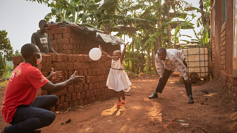 This photo shows a 3 year old girl wearing a white dress playing with a balloon with an African man wearing a CBM Tshirt.