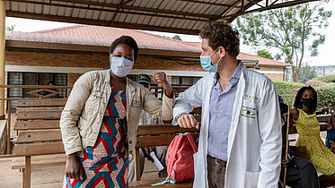 This photo shows a white doctor bumping elbows with a Black female patient wearing colourful traditional clothes.