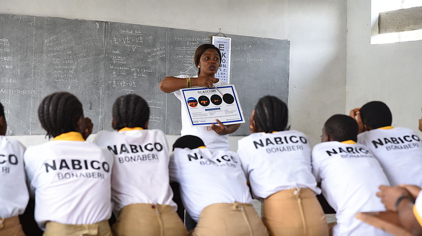 This photo shows a woman in a classroom holding up a sign with students watching her attentively.