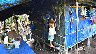 A girl affected by congenital cataract and a mental disability stands on a raised wood plank in her family's temporary shelter