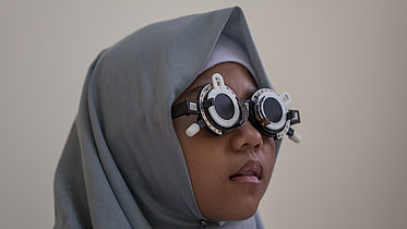 A girl from Indonesia wears special glasses to calculate an eyeglasses prescription.