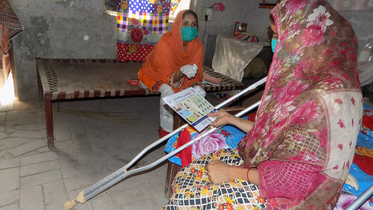 This photo shows 2 women - one with a physical disability, who is reading a COVID-19 information leaflet.