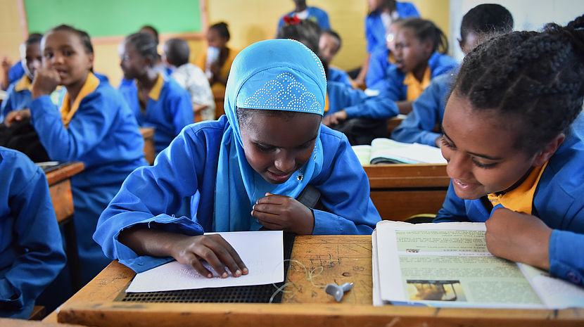 An 11 year old Ethiopian girl with a head scarf wearing a blue school uniform and reading a book in Braille, more students are in the background.