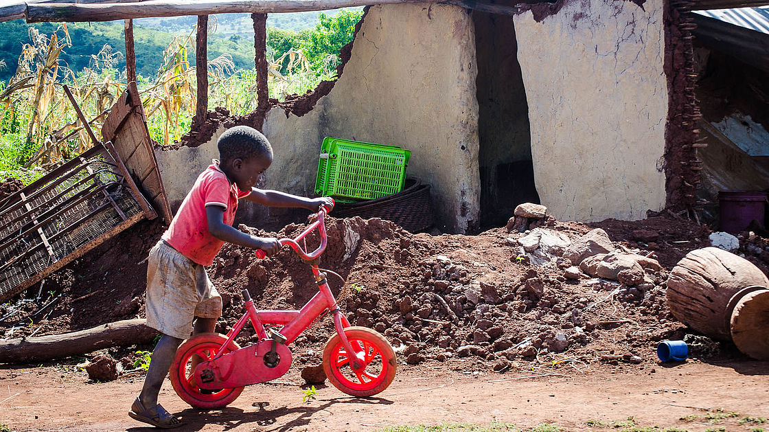 Son rides bicycle in front of his cyclone-damaged home