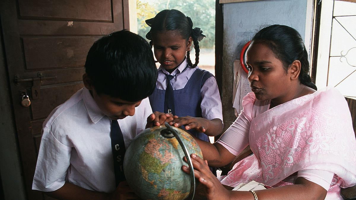 Low vision boy Karthik (11 years old) feeling the surface of a globe. A resource teacher is helping him. In the middle between them there is a classmate of Karthik. She is also touching the globe. The picture was taken in the resource room  of a school integrating handicapped children in Coimbatore, India.