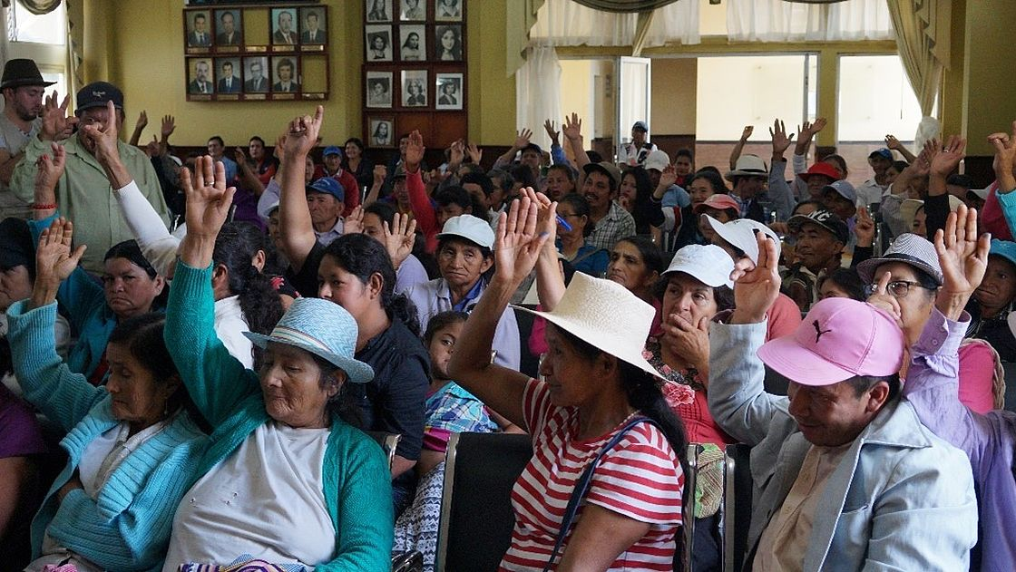 This photo shows Ecuadorians sitting in a room, some of them have their hands raised high - a vote is being carried out.