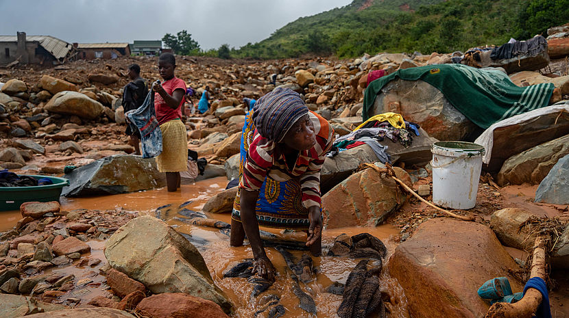 An elderly woman washes her belongings in the mud on March 19, 2019, in Chimanimani, Zimbabwe, after the area was hit by the Cyclone Idai © ZINYANGE AUNTONY / AFP
