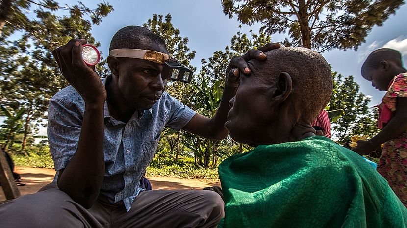 This photo shows a Ugandan man inspecting an old Ugandan woman's eyes in a field.