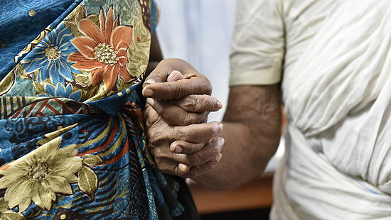 Mother and daughter hold hands the day after 75-year-old Thanka had cataract surgery at a CBM-supported hospital.