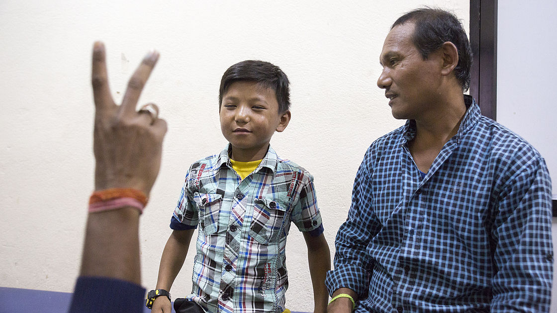 This photo shows a young boy's vision being checked, while his father looks on.
