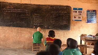 This image shows Assan sitting just a few inches away from the bloackboard in his classroom. He is sitting on a kitchen stool and copying the notes from the board.