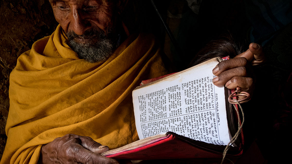 Ethiopian priest reads his books after receiving CBM-sponsored trichiasis surgery