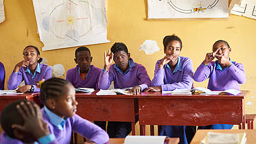 This image shows children in a classroom in Ethiopia, wearing a purple uniform. Some are signing with their hands.