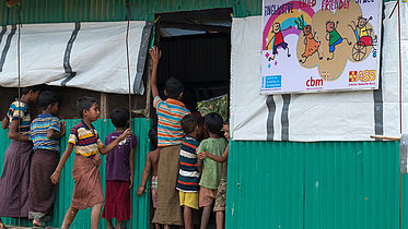 children at the door look inside as children play in the makeshift building