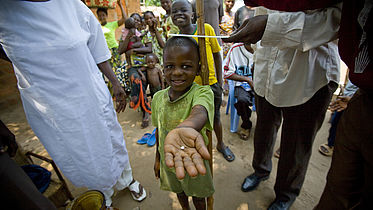 A young 7 year old boy holds out his hand, where there is a pill in his palm.
