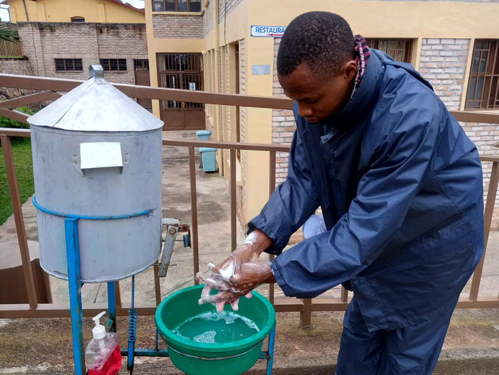 This photo shows a man washing his hands at a newly constructed (outdoor) hand washing station.