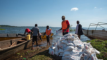 This photo shows a boat full of food material and packets, labelled CBM. Some men and unloading the boat. The Lake Victoria can be seen in the background.