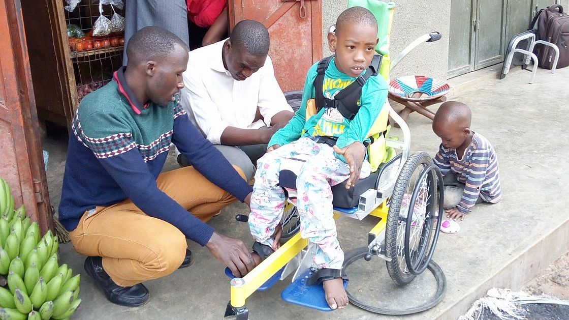 A man makes repairs to a wheelchair while showing the boy's father how to use the wheelchair footrest.