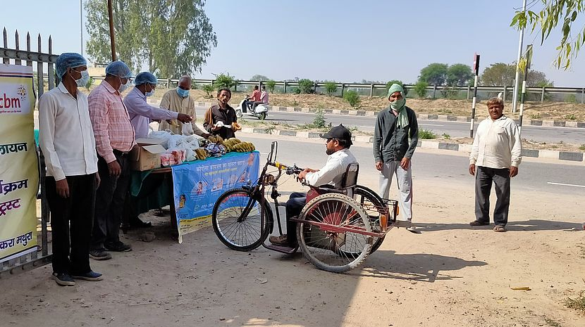 This photo shows a man in a tricycle approaching a cart full of fruits and vegetables at the side of a busy road. There are other men nearby. Everyone is wearing a mask and gloves.