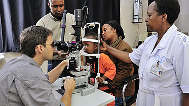CBM's Dr. Heiko Philippin and his team examine the eyes of Joyce (who had a successful bilateral cataract operation) at the KCMC Hospital, Tanzania