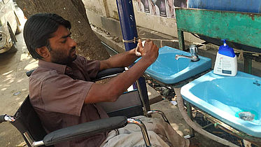 This photo shows a man sitting in a wheelchair, washing his hands at a wash basin with liquid soap.