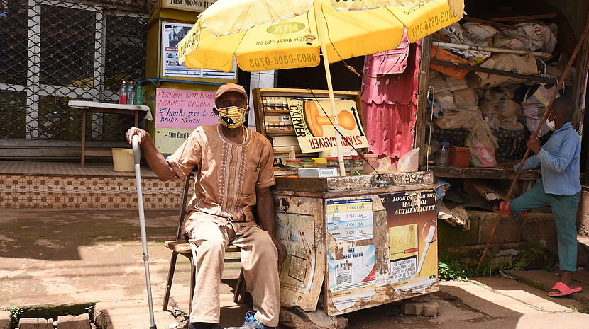 This photo shows a Cameroonian man in local attire sitting next to a mobile kiosk.