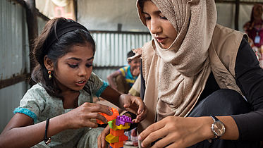 Child and teacher play in a child-friendly space in a Rohingya refugee camp ©CBM/ Hayduk