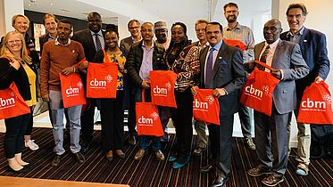 CBM staff attending the NNN gather for a group photo and show off bags with the CBM logo