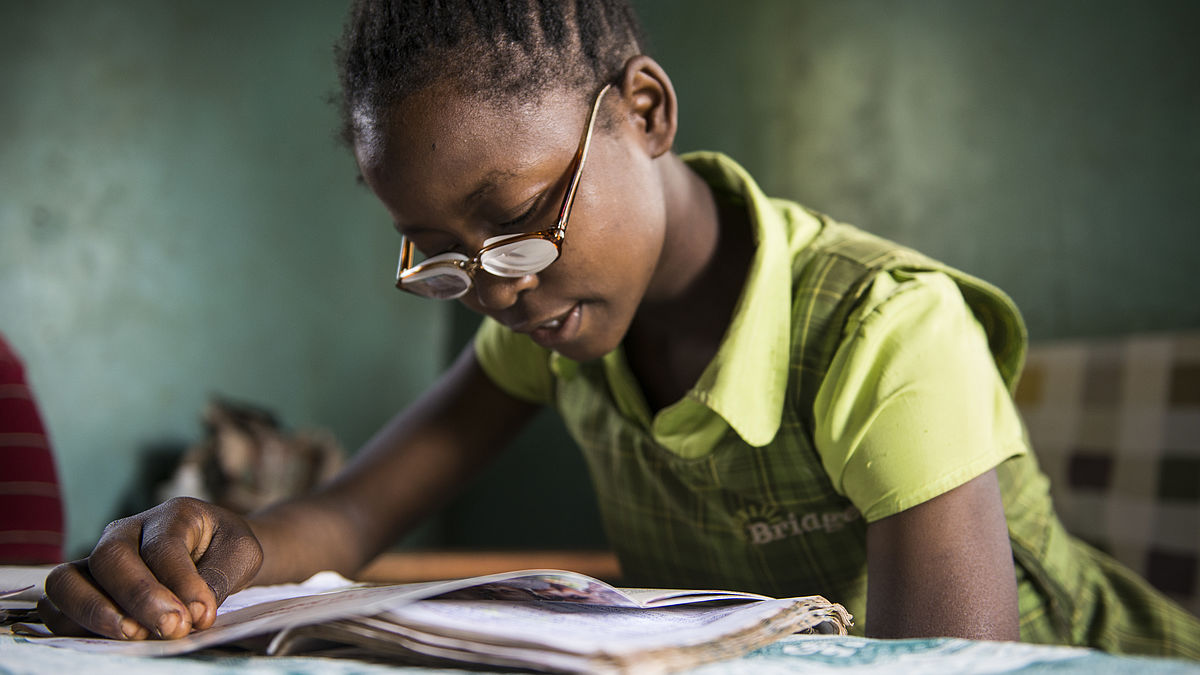 Christine is sitting on a table at home reading a book. She is using her new pair of glasses given by CBM partner, Sabatia Eye Hospital in western Kenya.