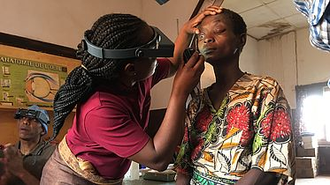 This photo shows a lady wearing googles inspecting the eyes of a patient.