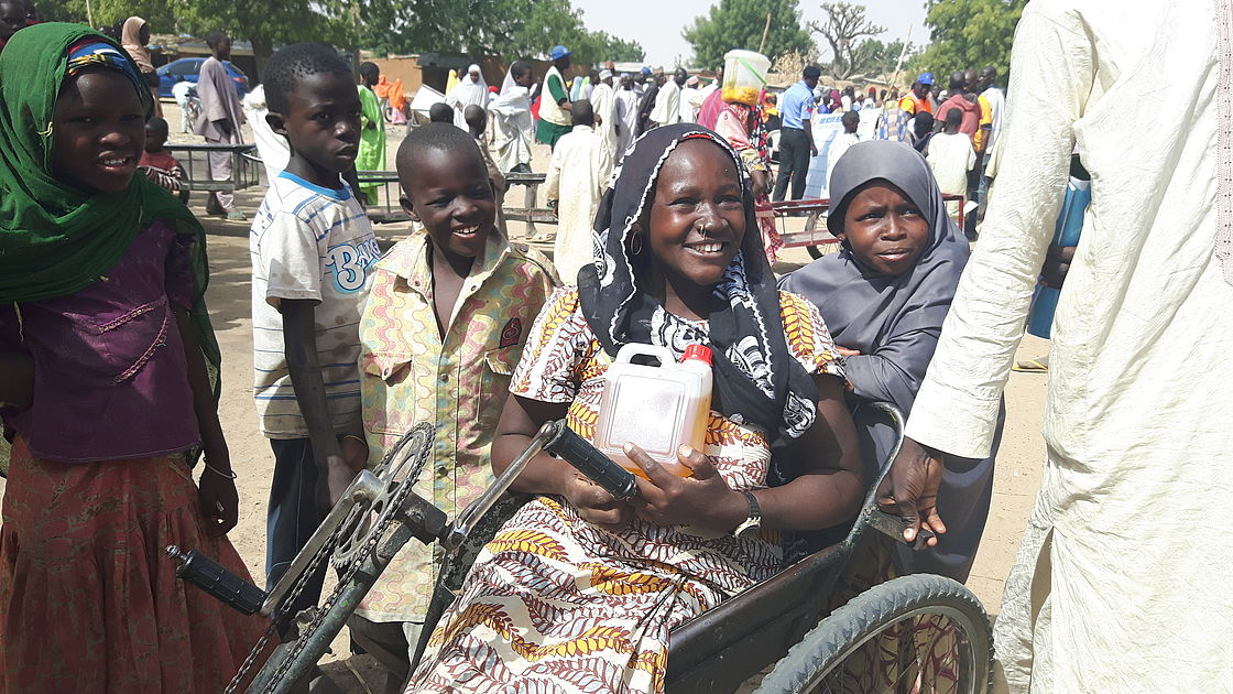 A woman smiling, holding household goods. (She uses a wheelchair)