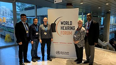 Group of people stand in front of a World Hearing Forum banner