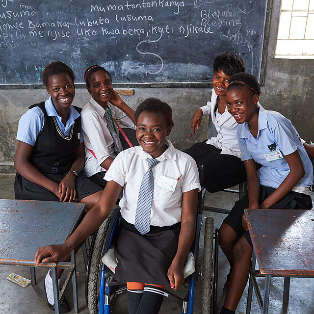 Abigail (sitting in her wheelchair) at school. In the background sit her four best friends: (from left to right) Rejoice, Abby, Agness und Taliya