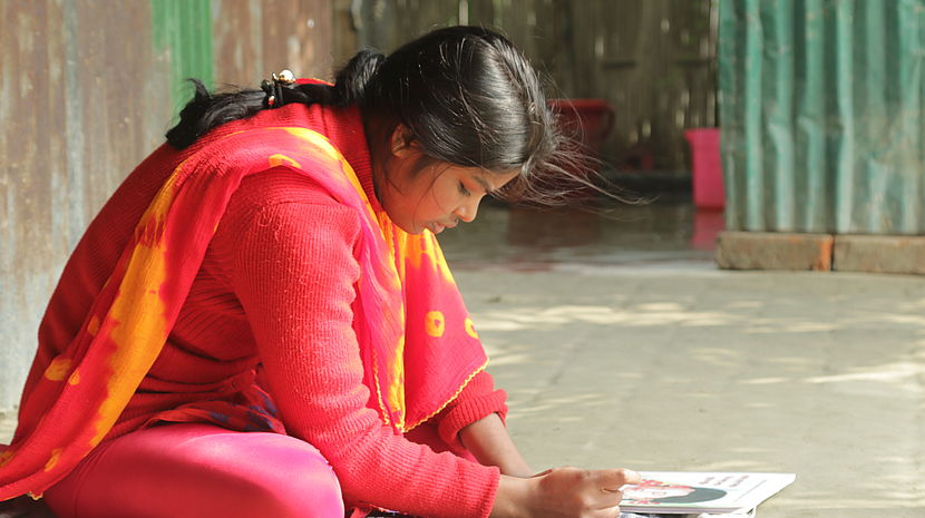 This photo shows a young girl sitting on the ground reading a text in Braille.