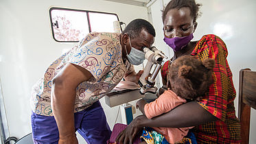 An eye nurse is examining a little baby's eyes in a mobile van which is a clinic.