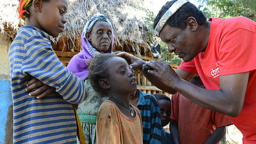 An Ethiopian man wearing a red CBM shirt is carrying out some eye tests on some young Ethiopian children, while an older lady looks on in the background.