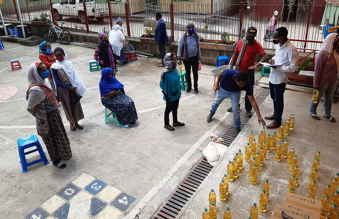 This photo shows people sitting far apart from each other. There are bottles of food oil and food packages ready to be distributed.