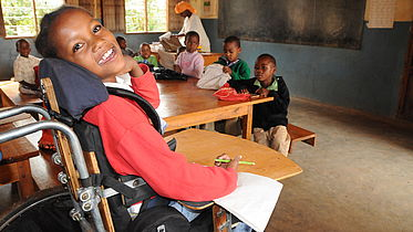 A young girl smiling happily in a classroom in Africa (she is a wheelchair user)