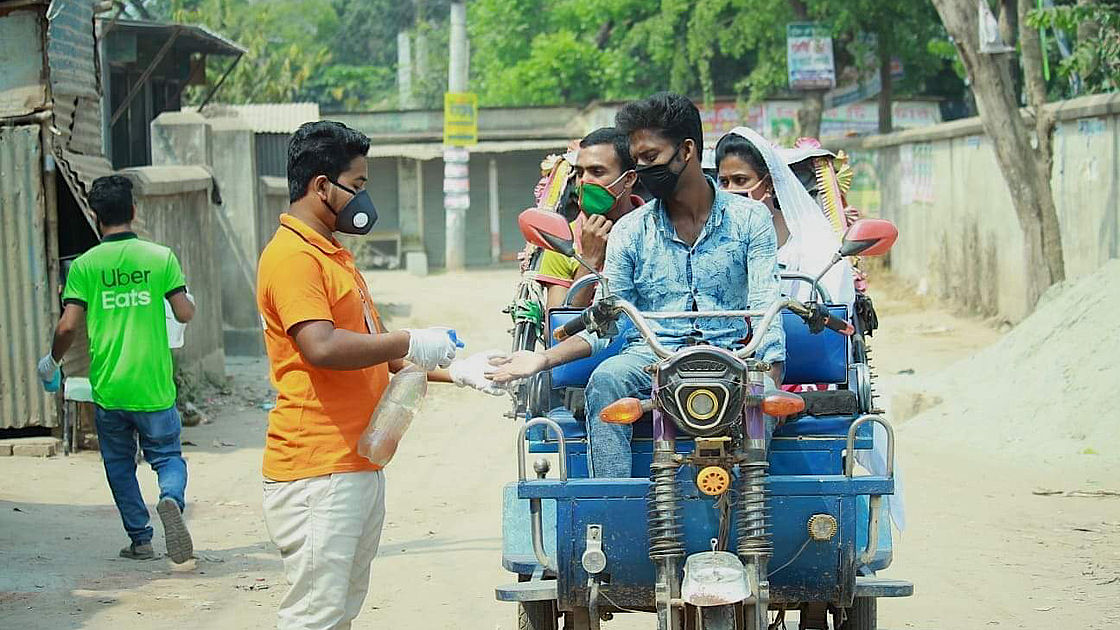 This photo shows a man spraying hand disinfectant on the hands of a rikshaw puller in Bangladesh. There are 2 women in the rikshaw. Everyone is wearing masks.