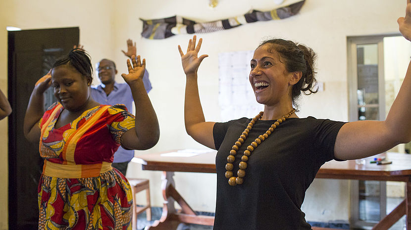participants laugh and raise their hands during a mental health workshop